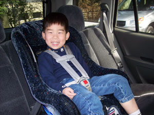 A Smiling Child Sits In Passenger Safety Seat